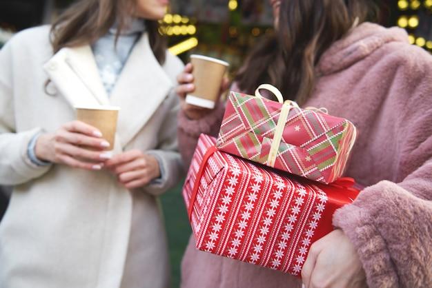 クリスマスプレゼントを運ぶクリスマスマーケットの2人の友人 無料写真