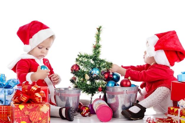 흰색 위에 두 재미있는 아기 소녀 산타 도우미 프리미엄 사진