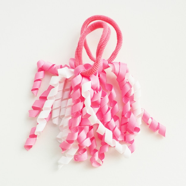 Two funny baby hair bands in the form of white and pink spiral ribbons. Premium Photo