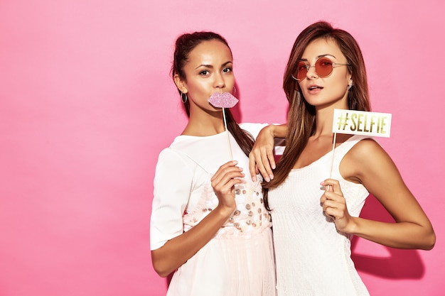 Two funny smiling women with big lips and selfie on stick. smart and beauty concept. joyful sexy young models ready for party. hot women isolated on pink wall. positive female Free Photo