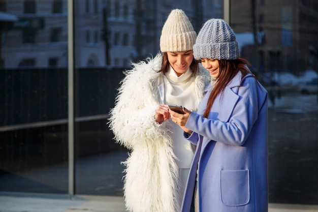 Two funny women friends laughing and sharing social media videos in a smart phone outdoors Premium Photo