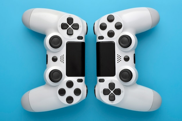 Two game controllers on blue background. game concept. competition concept. top view. Premium Photo