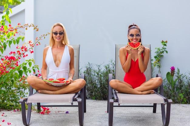 열대 국가에서 수박 휴일을 갖는 빌라에서 수영장에서 해변 의자에 수영복 아시아와 백인 두 여자 친구 신선한 과일 무료 사진