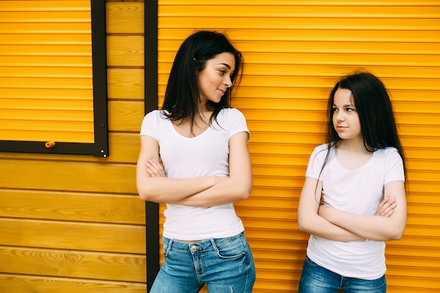 Two girl standing holding arms crossed Free Photo