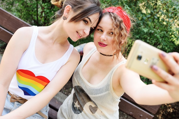 Two girlfriends lesbian relieve themselves on camera phones or taking selfies and smiling. Premium Photo