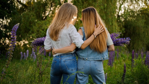 Two girlfriends standing on the field with bouquets of purple flowers Premium Photo