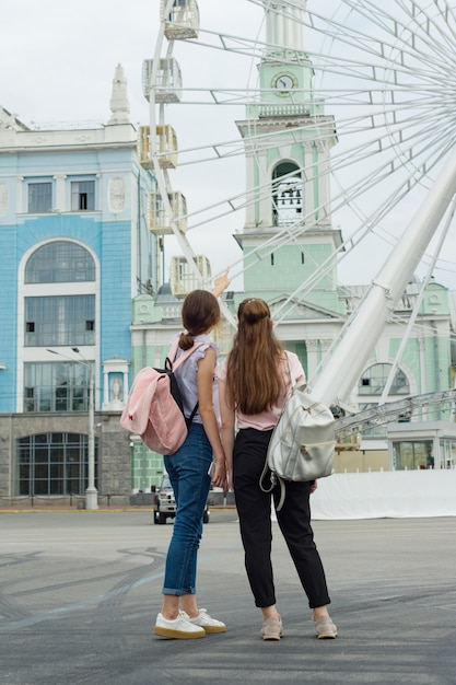 Two girls are looking at the ferris wheel Premium Photo