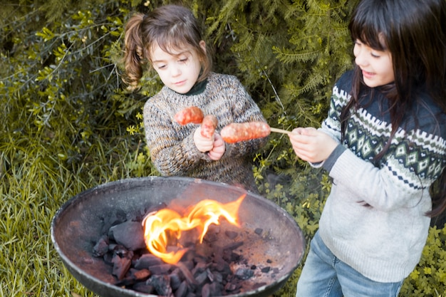 Two girls burning sausages on barbeque in park Free Photo