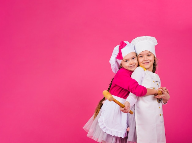 Two girls cooks with kitchen utensils hugging Free Photo