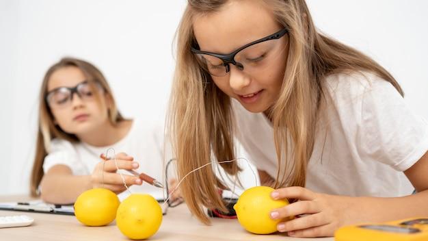 電気とレモンで科学実験をしている2人の女の子 無料写真