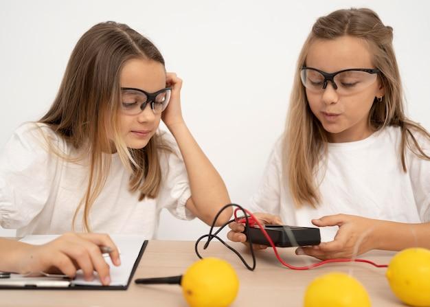 레몬과 전기로 과학 실험을하는 두 소녀 무료 사진