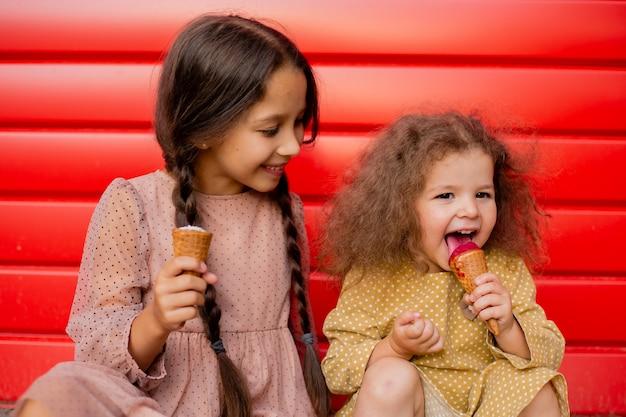 Две девушки едят мороженое и дурачатся. подросток и маленькая девочка на фоне красной стены. Premium Фотографии