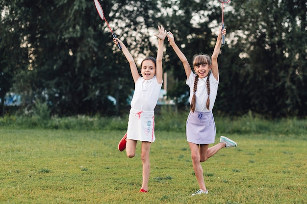 Two girls enjoying in the park holding badminton Free Photo
