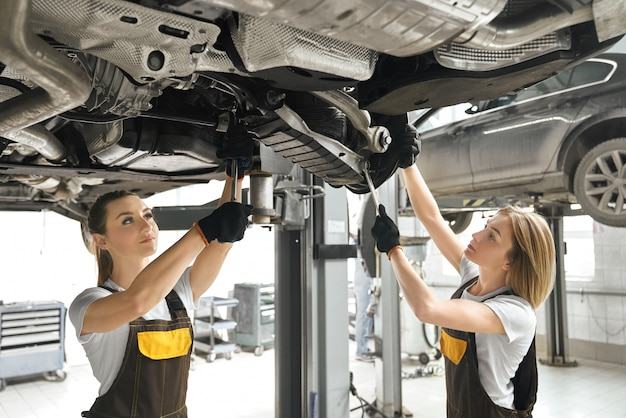Two girls fixing lifted auto undercarriage, using wrenches. Free Photo