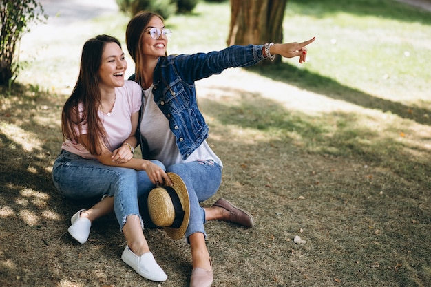 Two girls friends sitting in park Free Photo