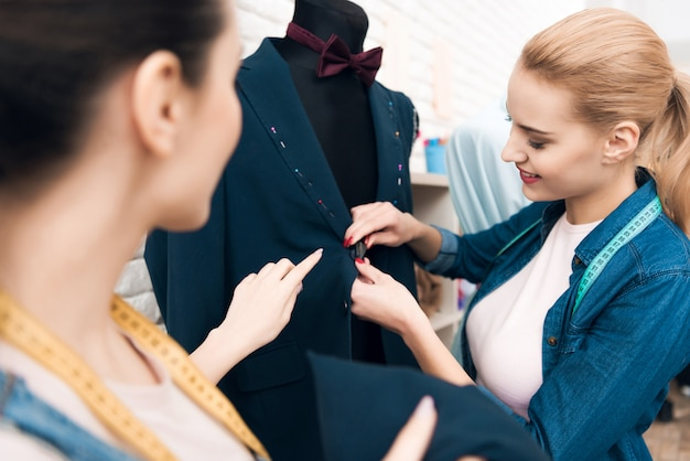 Two girls at garment factory desining new man suit jacket Premium Photo