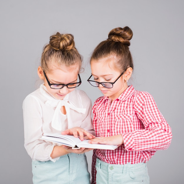 Two girls in glasses reading book Free Photo