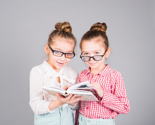 Two girls in glasses standing with book Free Photo