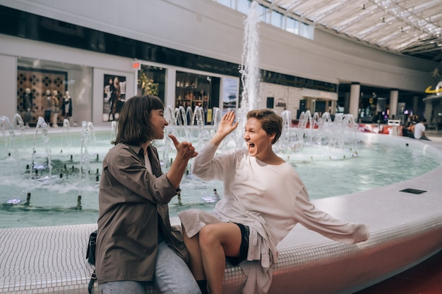 Two girls have fun in the mall, next to a fountain Free Photo