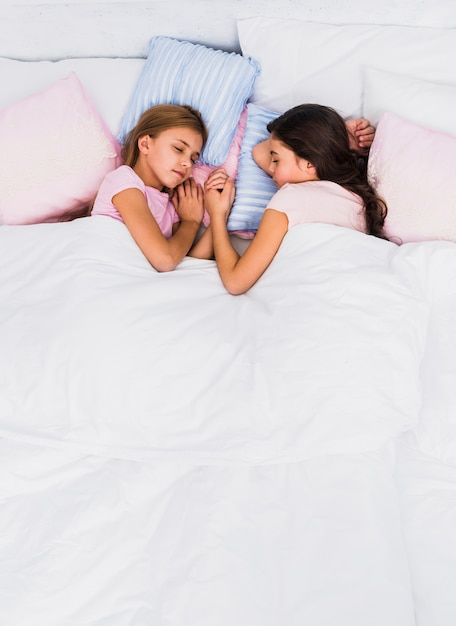 Two girls holding each others hand sleeping together on