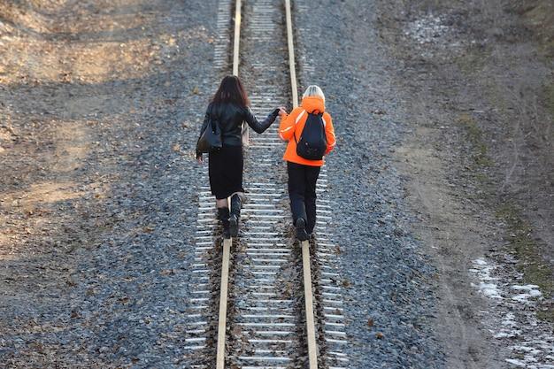 철도에 걸어 손을 잡고 두 여자 프리미엄 사진