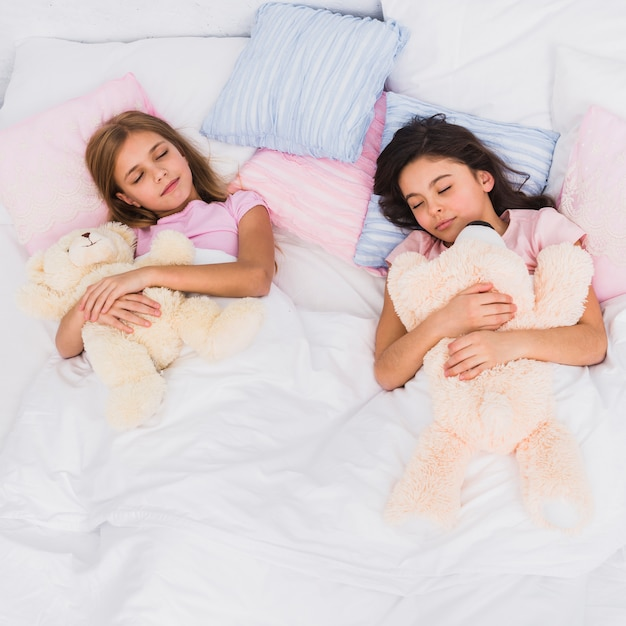Two girls holding teddy bear in hand sleeping together on bed Free Photo