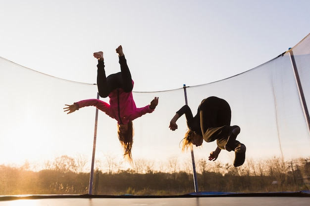 Two girls jumping on trampoline at sunset Free Photo
