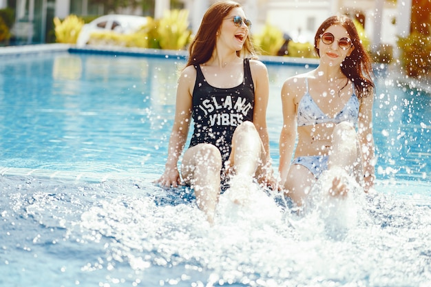 Two girls laughing and having fun by the pool Free Photo