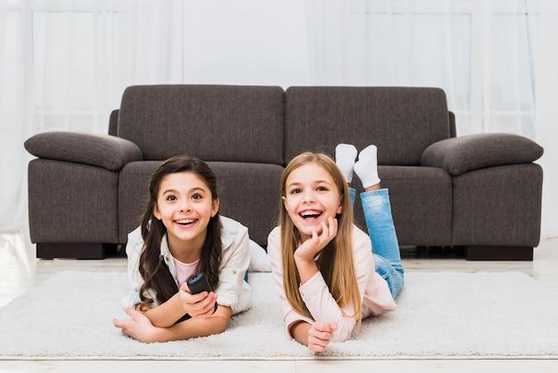 Two girls lying on carpet enjoying watching the television Free Photo