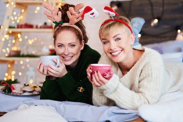 ベッドに横になってお茶を飲む2人の女の子 無料写真