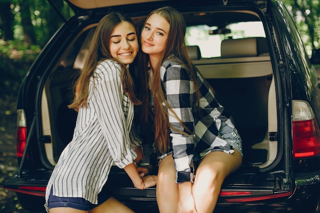 Two girls near car Free Photo