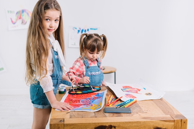 Two girls painting with aquarelle on paper Free Photo