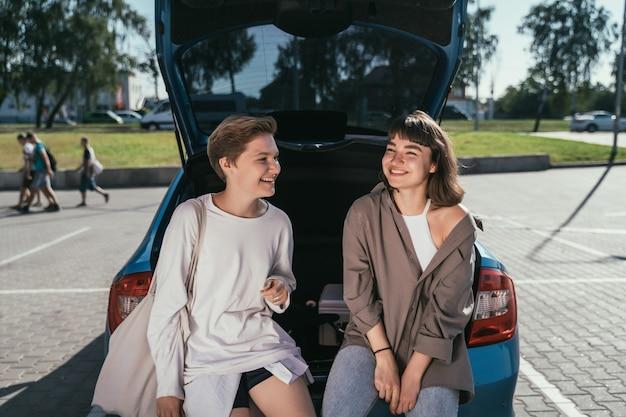 Due ragazze nel parcheggio alla posa aperta del tronco Foto Gratuite