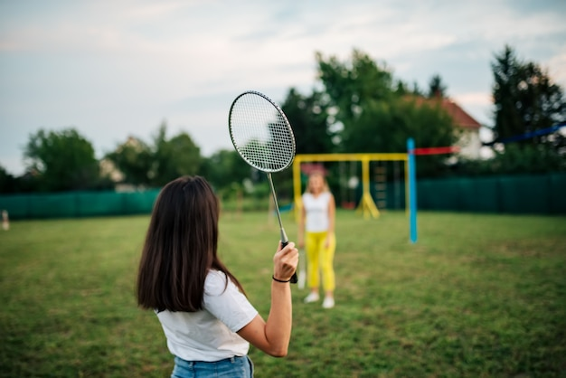 Two girls playing badminton on a green field. Premium Photo