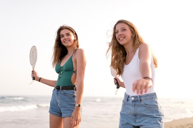 ビーチでテニスをする2人の女の子 無料写真