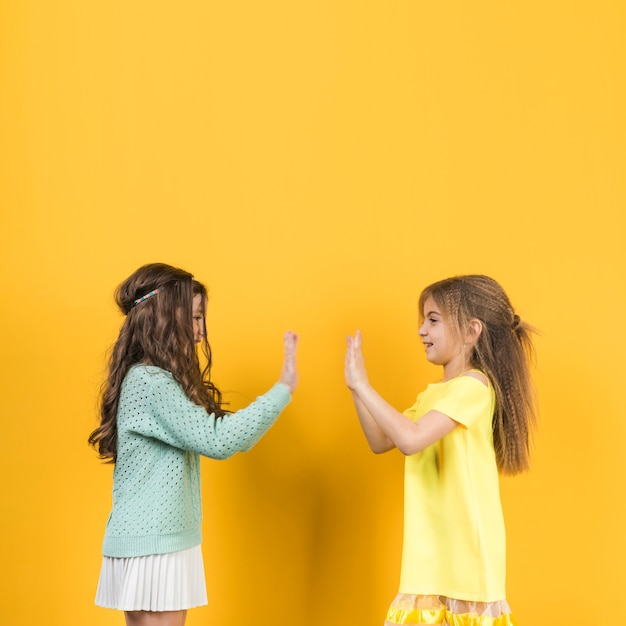 Two girls playing clapping hands Free Photo