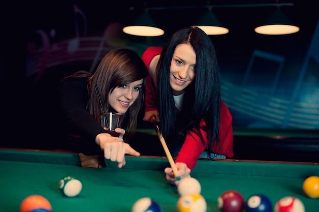 Due ragazze che giocano a biliardo Foto Gratuite