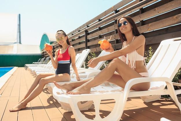 Le due ragazze giocano e si rilassano in piscina durante le vacanze estive Foto Gratuite