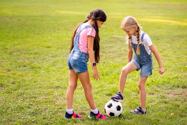 Two girls playing with soccer ball on grass Free Photo
