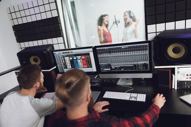 二人の女の子がレコーディングスタジオで歌います。 Premium写真