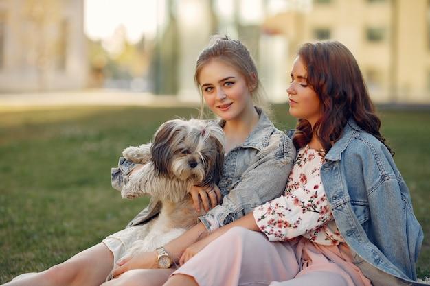 Две девушки сидят в парке с маленькой собачкой Бесплатные Фотографии