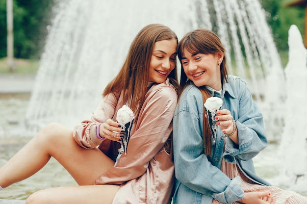 Two girls sitting near the fountain and going ice cream. Free Photo