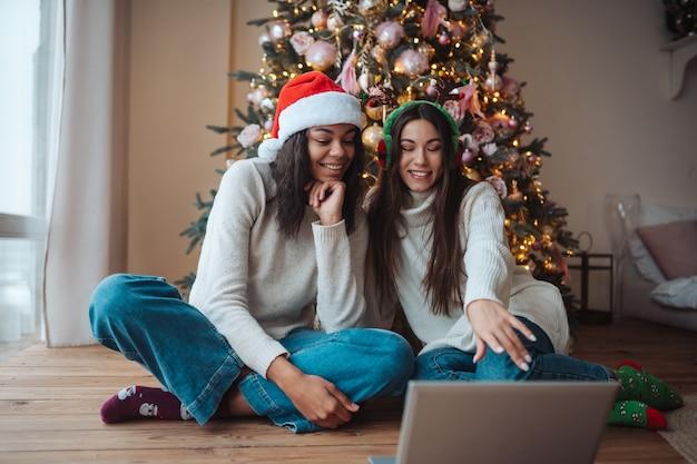 집에서 크리스마스 축하 기간 동안 노트북에서 온라인 친구와 이야기하는 동안 웃는 두 여자 무료 사진