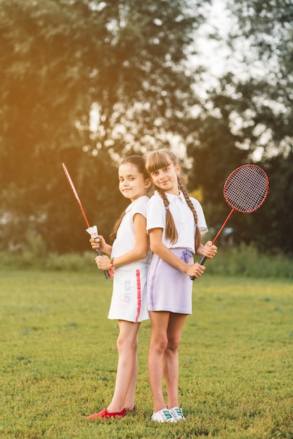 Two girls standing back to back holding badminton in the park Free Photo