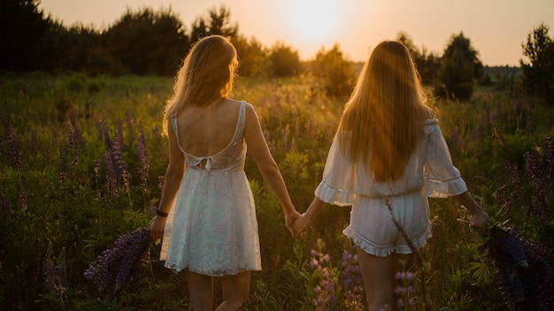 Two girls standing on the field with bouquets of purple flowers Premium Photo