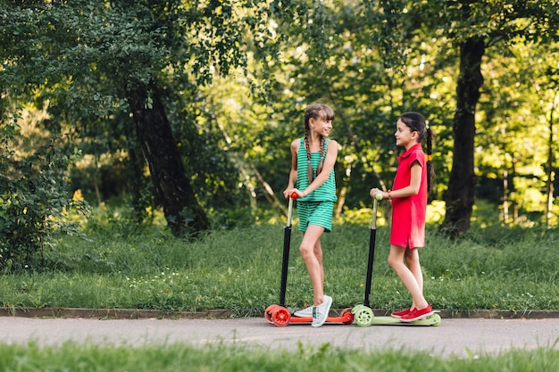 Two girls standing on kick scooter at countryside road Free Photo