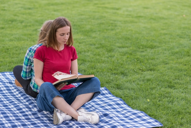 Two girls studying outdoors on picnic blanket Free Photo