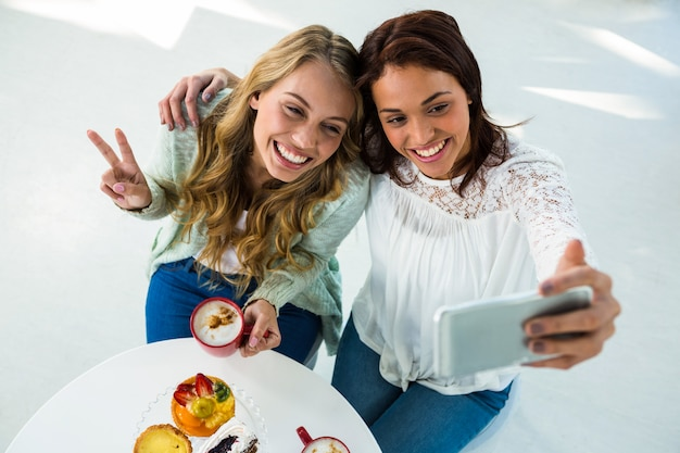 Two girls take a selfie while eating and drinking coffee Premium Photo
