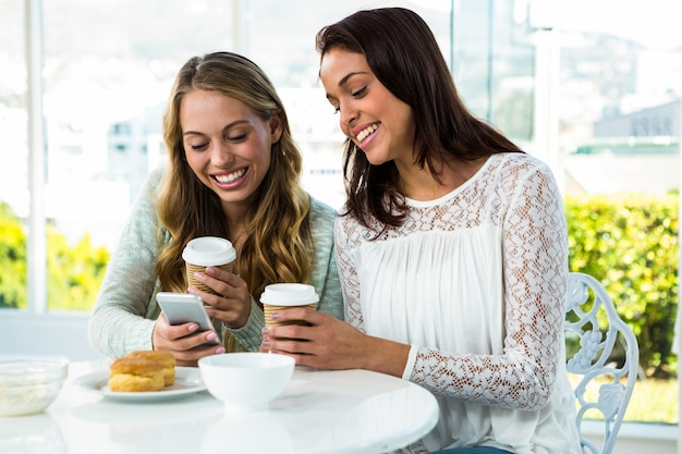 Two girls use a phone while eating and drinking Premium Photo