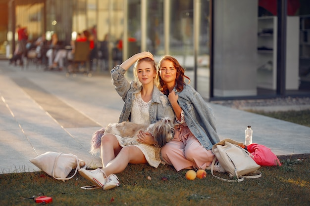 Two girls wallking in a park with a little dog Free Photo